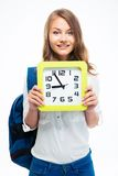 Girl with backpack holding big clock Royalty Free Stock Photography