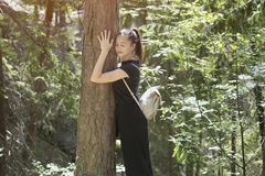 Girl with a backpack is hugging a tree with her eyes closed in t. He forest. Summer sunny day royalty free stock photos