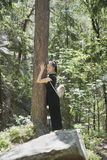 Girl with a backpack is hugging a tree with her eyes closed in t. He forest. Summer sunny day stock image
