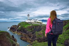 Girl with a backpack looking the Fanad Head Lighthouse in Ireland stock image