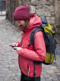 The girl with the backpack looks in the phone. Royalty Free Stock Photos
