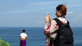 Girl with backpack and a man in sarong taking photos with their phones stock footage