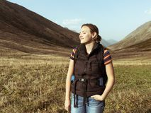 Girl with a backpack in a mountain hike royalty free stock images