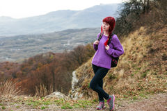 Girl backpack on a mountain. Girl with red hair and a backpack on a mountain Stock Photo