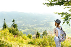 Girl with backpack in mountain. Stock Images