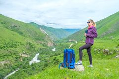 Girl with a backpack in the mountains. stock photo