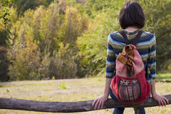 The girl with the backpack resting in the forest. Royalty Free Stock Photo