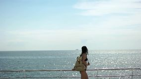 Girl with backpack at the sea stock footage