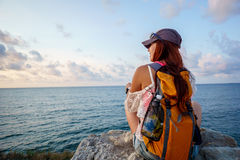 Girl with backpack sitting on rock and looking at sea Royalty Free Stock Image
