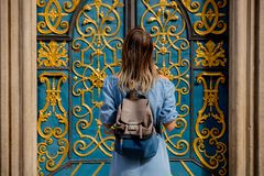Girl with a backpack standing near a beautiful door royalty free stock image