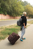 Girl with a backpack and a suitcase. Is on the road Stock Photography