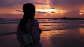Girl with backpack at sunset near the ocean.  stock video footage