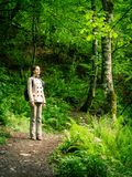 Girl with a backpack on the tourist trail in the spring forest stock photo