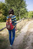 Girl with backpack is traveling in the woods. Royalty Free Stock Images