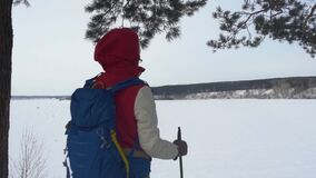Girl with backpack trekking in mountains. Cold weather, Snow on hills. Winter hiking.A woman with a backpack admires the. View of the winter mountains stock video