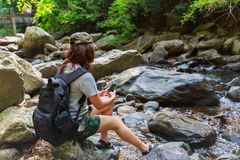Girl with backpack using smart phone during trekking trip. Stock Photos