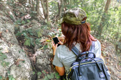 Girl with backpack using smart phone during trekking trip. Royalty Free Stock Photo