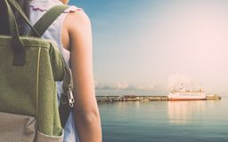 Girl with backpack waiting for a cruise ship at sea port. Royalty Free Stock Image