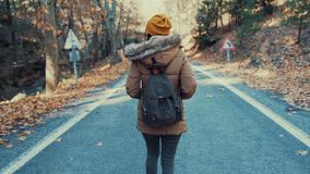 Girl with backpack is walking on country road in autumn stock footage