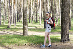 Girl with backpack is walking in the forest Royalty Free Stock Photo