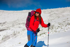 Girl with backpack walking on snow in the mountains. Girl with backpack walking on snow in the mountains and mountain climbing during the winter holidays Stock Image