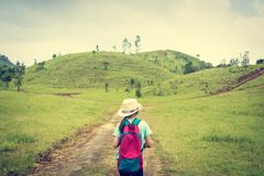 Girl with backpack walking in to bald hill. Stock Photography