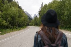 A girl with a backpack walks along the mountain path. A woman is walking along a stony road. The blonde travels to royalty free stock photo