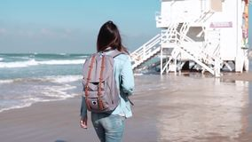 Girl with backpack walks by coast guard post. Freedom. Hair blowing in wind. Woman wanders on the beach. Slow motion. Girl with backpack walks by coast guard stock video