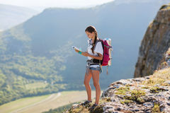 Girl with a backpack. Young, beautiful girl with a backpack on her back, studying a map while standing on the plateau. In the background, green meadows and Royalty Free Stock Image