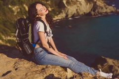 Girl backpacker is sitting on rock over sea view Stock Photography