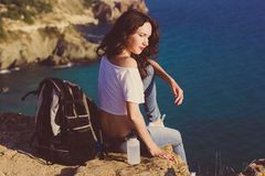 Girl backpacker is sitting on rock over sea view Royalty Free Stock Image
