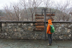 Girl-backpacker stands in front of pointers to the gift shops, horizontal Royalty Free Stock Image