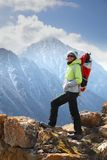 A girl backpacker stands on top of a mountain Royalty Free Stock Images