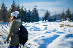 Girl backpacker walking in winter mountain forest Royalty Free Stock Photography