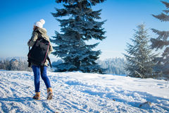 Girl backpacker walking in winter mountain forest Royalty Free Stock Image