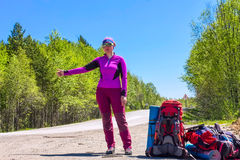 Girl with backpacks hitchhike a car on the road. Girl in purple with backpacks hitchhike a car on the road Royalty Free Stock Photography