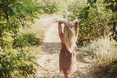 Girl backs on a path in the woods. Blonde girl standing back on a path in summer forest royalty free stock photos