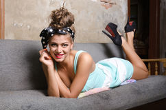 Girl on bad. Pin up model lies on old bed Stock Photography