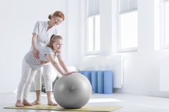 Girl with bad posture exercising. Little girl with bad posture doing exercises with ball royalty free stock image