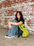 Girl with bag 5. Girl with bookbag sitting against a brick wall Royalty Free Stock Photography