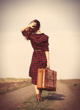 Girl with bag. Beautiful girl in plaid dress with bag on countryside Stock Image