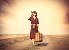 Girl with bag and binocular. Beautiful girl in plaid dress with bag and binocular on countryside stock image