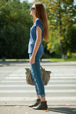 Girl with a bag goes the way of pedestrian zebra Stock Image