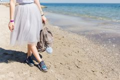 Girl with bag in hand standing on weat sand near sea. View of the legs in a lush gray skirt and sneakers.  stock photos