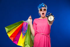 Girl with bags and an alarm clock in hands. On a blue background Stock Images