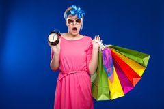 Girl with bags and an alarm clock in hands. On a blue background Stock Photo