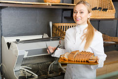 Girl baker cutting bread on machine Royalty Free Stock Photo