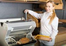 Girl baker cutting bread on machine Stock Photos