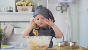 Girl baker mixes the mixture for cookies with a big spoon. Close up Royalty Free Stock Photo