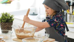 Girl baker mixes the mixture for cookies with a whisk. Close up Royalty Free Stock Images